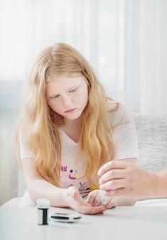 Medición del nivel de azúcar en la sangre de una niña adolescente con glucómetro