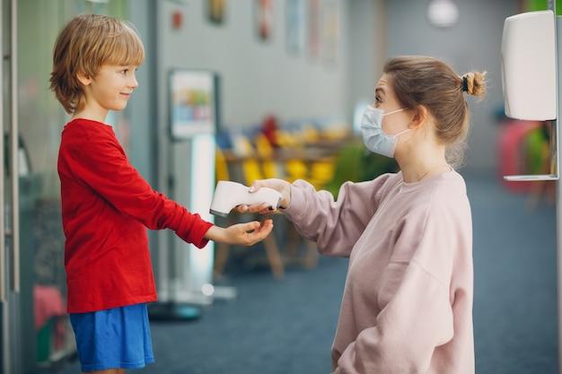 Medición de la temperatura infantil por termómetro láser en la escuela primaria mujer en mascarilla