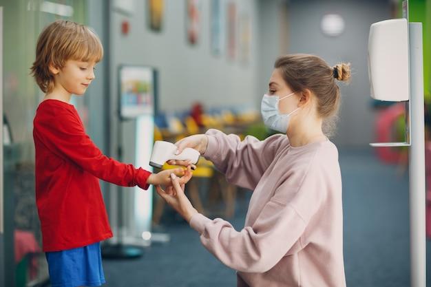 Medición de la temperatura infantil con termómetro láser en la escuela primaria