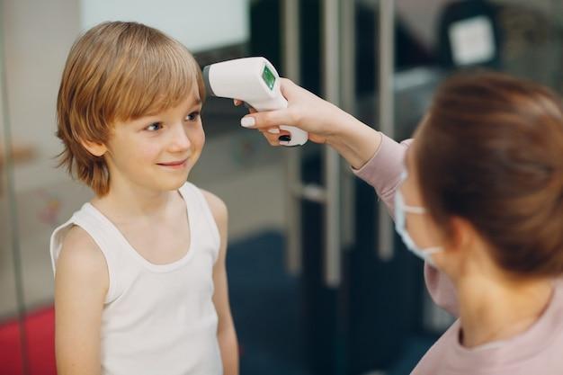 Medición de la temperatura infantil con termómetro láser en el jardín de infantes