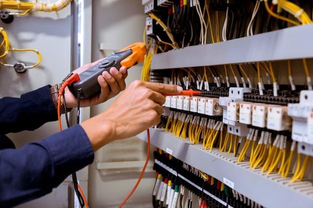 Mediciones de electricista con multímetro que prueba la corriente eléctrica en el panel de control