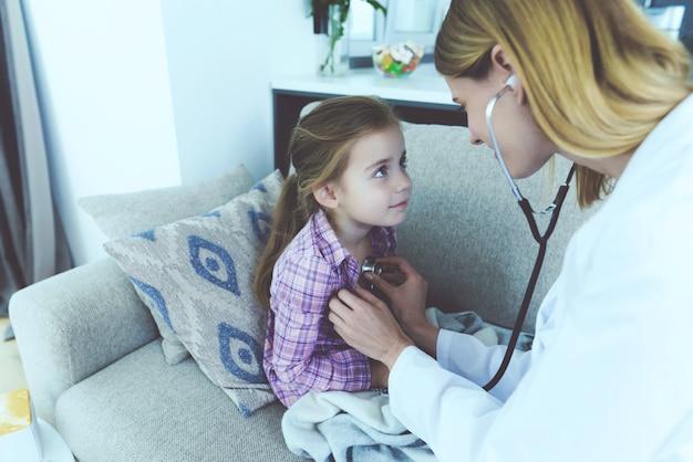 Un médico se acercó a ella y la escuchó con un estetoscopio.
