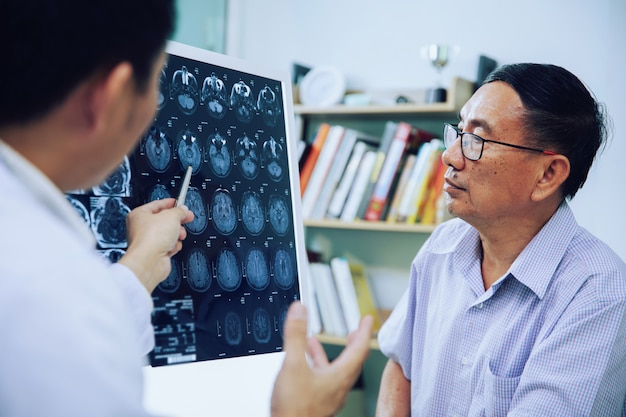 El médico aconseja a un paciente anciano acerca de las exploraciones cerebrales de resonancia magnética (rayos x)