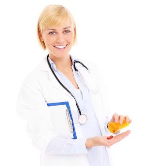 Un médico adulto con estetoscopio y pastillas de pie sobre fondo blanco.
