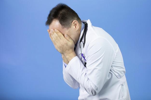 Médico adulto con expresión triste que cubre la cara con las manos mientras llora.