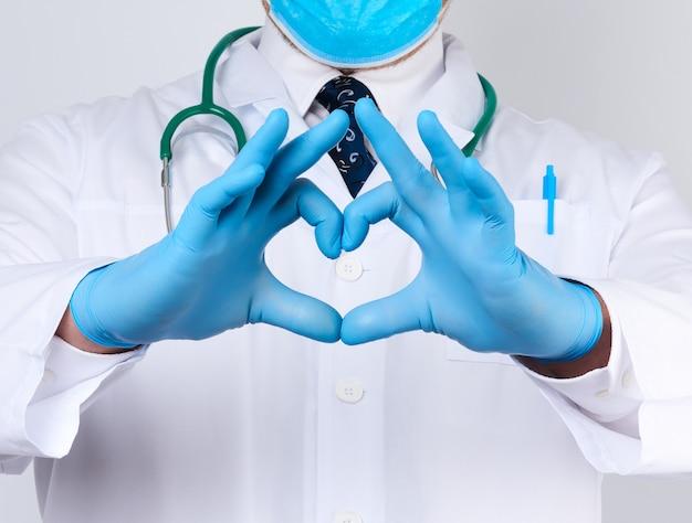 Médico adulto hombre en una bata blanca médica con un estetoscopio en el cuello muestra un gesto de corazón con las manos