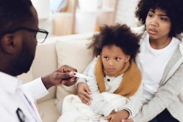 Médico africano toma la temperatura del niño enfermo con gripe.