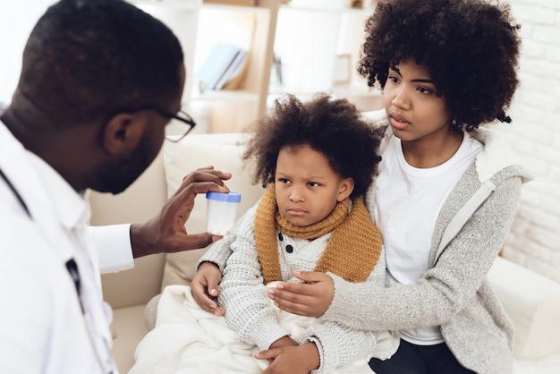 Médico afroamericano le da pastillas a un niño enfermo con gripe.