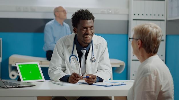Médico afroamericano discutiendo con mujer mayor