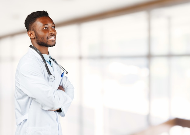 Médico afroamericano con un estetoscopio de pie contra el fondo borroso