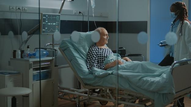 Médico afroamericano fijación de cama ajustable en la sala del hospital