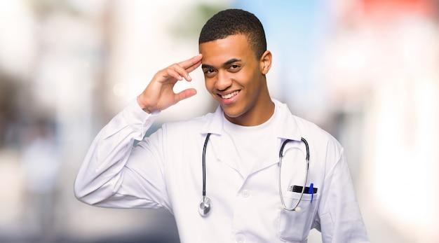 Médico afroamericano joven saludando con la mano al aire libre