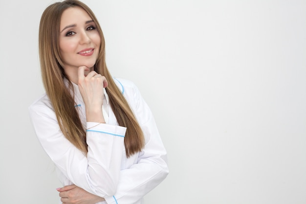 El médico aislado en un fondo blanco, la niña en una bata blanca sonríe y mira en el marco, con copia espacio. concepto de publicidad clínica.