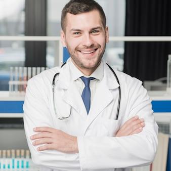 Médico alegre de pie con los brazos cruzados