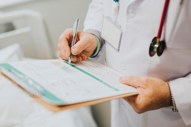 Médico anotando los síntomas de un paciente.