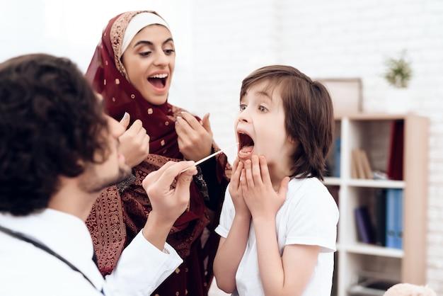 Un médico árabe diagnostica a un niño pequeño.
