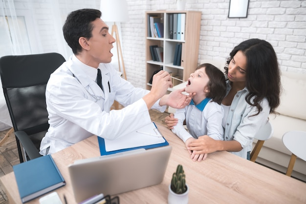 Médico árabe está haciendo una prueba de garganta para el niño.