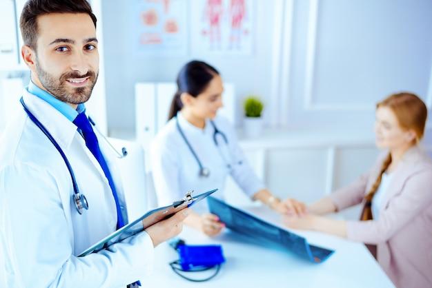 Médico árabe en la oficina con tableta y estetoscopio, enfermera trabajando con el paciente en el fondo