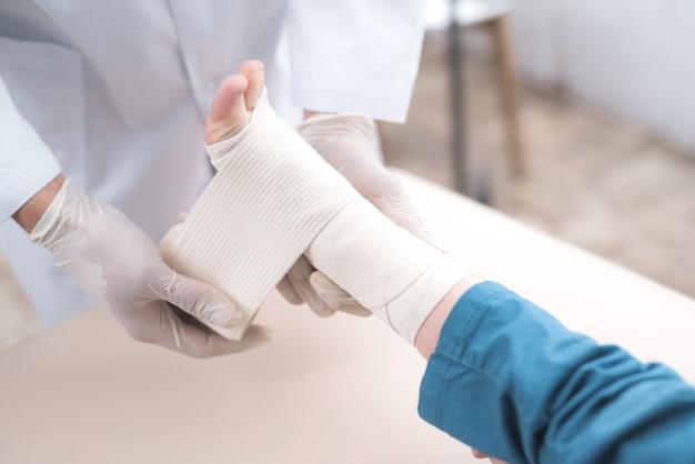 Médico árabe está vendando la pierna de niño pequeño.