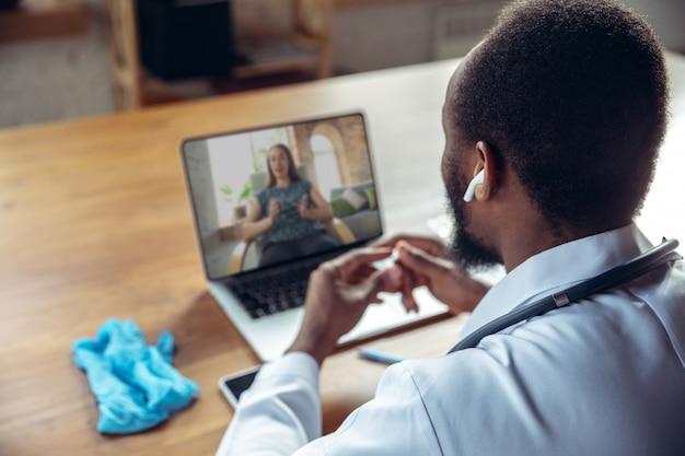 Médico asesorando al paciente en línea con una computadora portátil