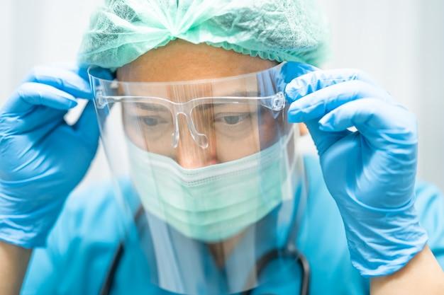 Médico asiático con careta y traje de ppe para verificar que el paciente protege el coronavirus covid-19.