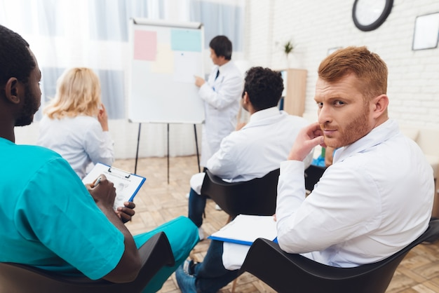 Médico asiático comparte experiencia con colegas.