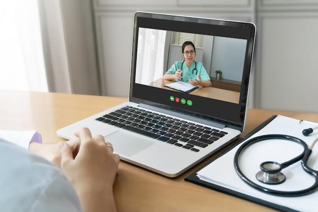 El médico asiático y el equipo médico hacen una videoconferencia para informar, debatir y consultar sobre el virus de la pandemia en una reunión en la sala médica.
