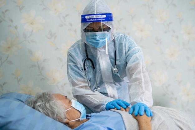 Médico asiático que usa protector facial y ppe se adapta a la nueva normalidad para verificar que el paciente protege la infección de seguridad covid-19 brote de coronavirus en la sala de enfermería de cuarentena.