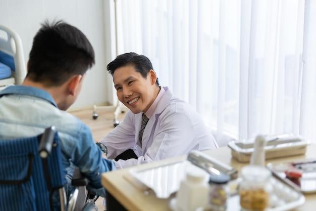 Médico asiático revisando, consultando y alentando a un paciente joven discapacitado