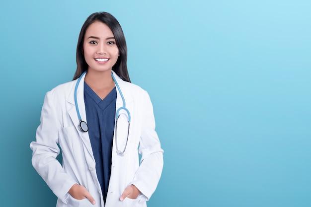 Médico asiático sonriente de la mujer en una capa blanca