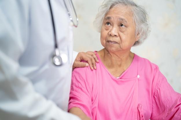 Médico asiático tocar paciente mujer mayor asiática con amor.