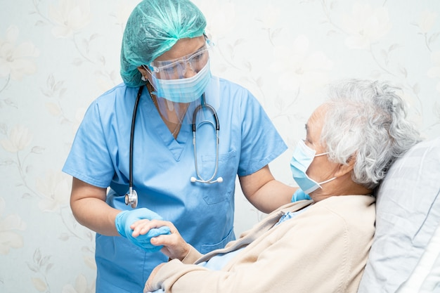 Médico asiático vistiendo careta y traje de ppe para revisar al paciente