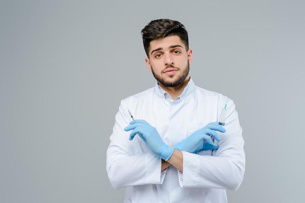 Médico atractivo en guantes con suringes aislados sobre fondo gris