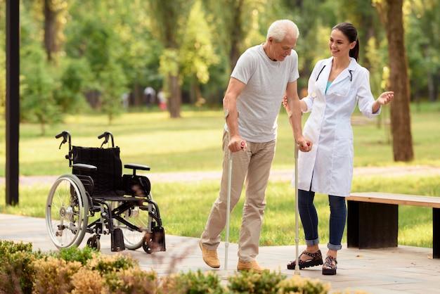 El médico ayuda al paciente a caminar con muletas.