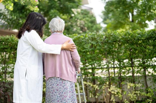 Médico ayuda y cuidado mujer mayor asiática usa andador en el parque