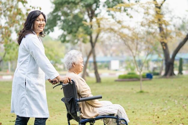 Médico ayuda y cuidado paciente asiático mayor o anciano sentado en silla de ruedas en el parque en la sala del hospital de enfermería, concepto médico fuerte y saludable.