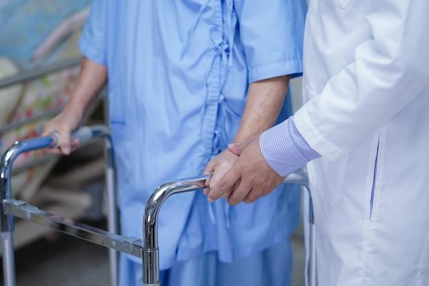 Médico ayuda a paciente mayor o anciana asiática a caminar con andador en la sala del hospital de enfermería.