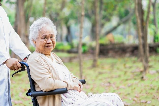 Médico ayuda a paciente mujer mayor asiática sentada en silla de ruedas en el parque.