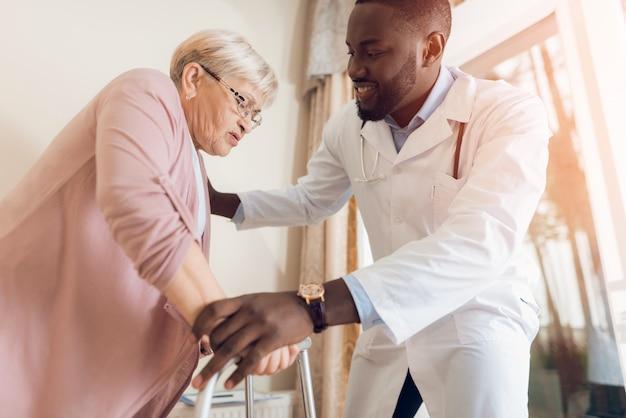 El médico ayuda a salir de la cama a una mujer mayor.