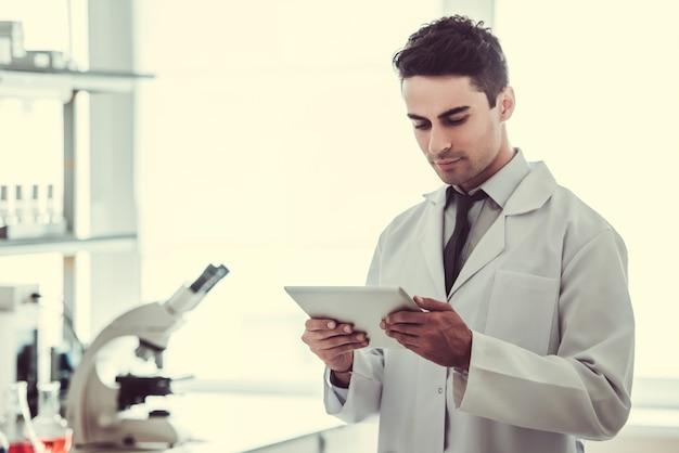 Médico en bata blanca está utilizando una tableta digital.