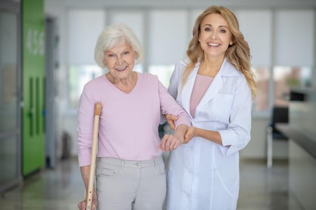 Médico en una bata de laboratorio apoyando a su paciente y ambos sonriendo