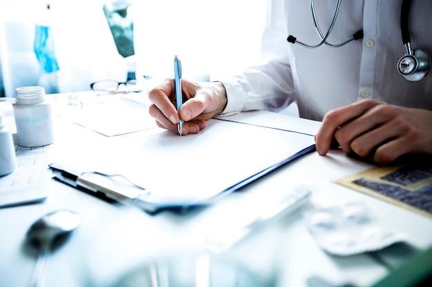 El médico de la bata de laboratorio escribe una receta en una hoja de papel, sentado en la mesa de la clínica.