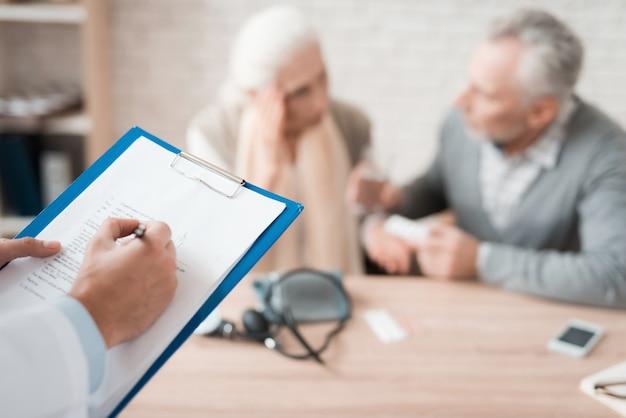 Médico calificado toma notas mientras examina pareja de ancianos.