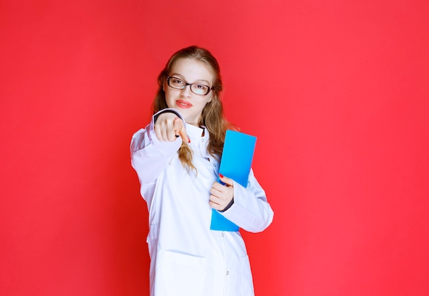 Médico con una carpeta azul saludando a su paciente.