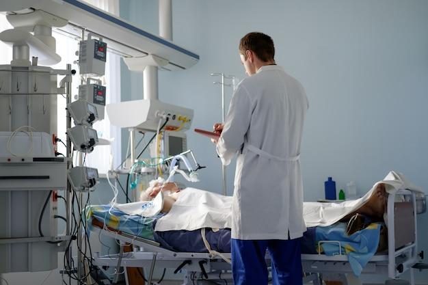 El médico caucásico de cuidados intensivos examina la postura crítica entubada del paciente escribiendo notas al informe del caso en el departamento de cuidados intensivos