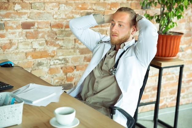 Médico caucásico descansando después de consultar al paciente que trabaja en el gabinete