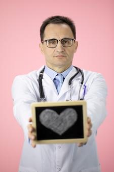 Médico caucásico con estetoscopio en una bata blanca en la pared rosa tiene corazón