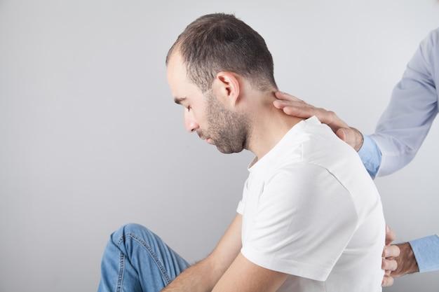 Médico caucásico masajeando el cuello del hombre.