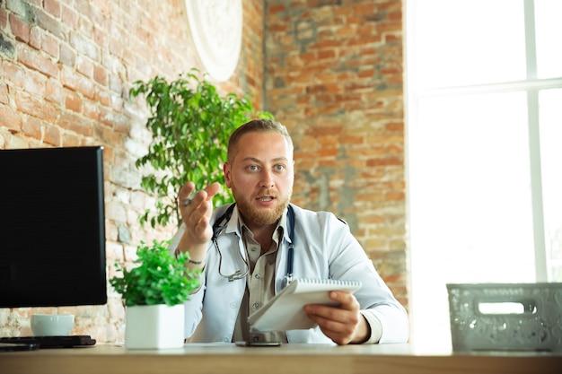 Médico caucásico que consulta para el paciente explicando la receta del fármaco que trabaja en el gabinete