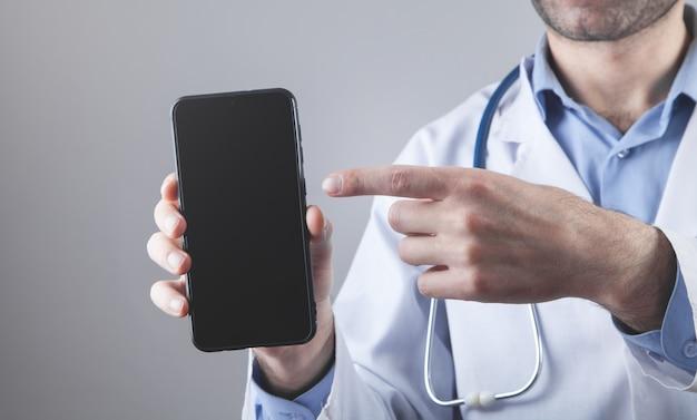 Médico caucásico sosteniendo un teléfono inteligente negro.